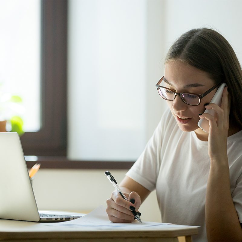 Busy female worker talking over phone, consulting client, solving company problems, giving help and assisting while writing down important information. Call center operator